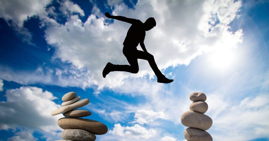 Man jumping between rocks taking risks
